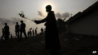 """A Sri Lankan ethnic Tamil Catholic devotee swings a container of incense smoke during the annual feast at the St. Anthony""""s Church in Kachchathivu, about 340 kilometers (211 miles) north of Colombo, Sri Lanka, Sunday, March 4, 2012"""