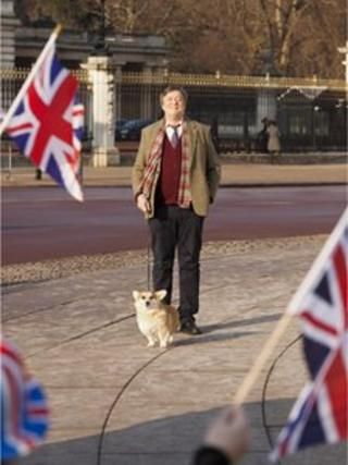 Stephen Fry at Buckingham Palace with a corgi. Photo: VisitEngland