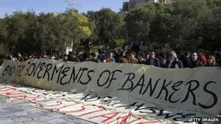 Leftist demonstrators hold a banner at the entrance to the Acropolis archaeological site, reading in English: 'End the governments of bankers'