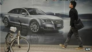 A pedestrian passes a billboard for a foreign car on a street in Shanghai