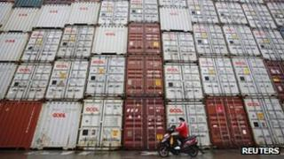 A woman rides her motorcycle past shipping containers at the Port of Shanghai (file image)