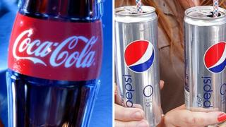 A bottle of Coca Cola beside two silver cans of Diet Pepsi