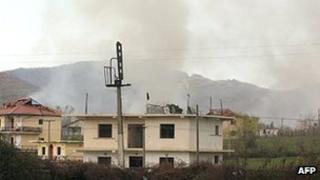 Smoke rising behind damaged buildings