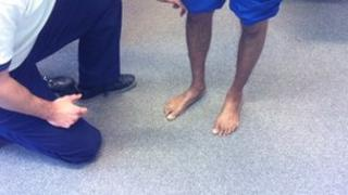 Physiotherapist examines man's ankles