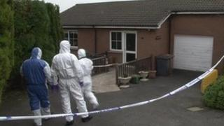 Forensics officers at the scene of the house fire