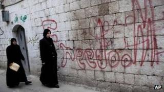 "Women walk past graffiti saying ""Freedom"" in the Syrian city of Idlib (11 March 2012)"