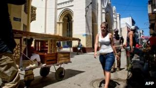 Cubans walk next to Our Lady of Charity church, occupied by 13 Cuban dissidents on 14 March, 2012