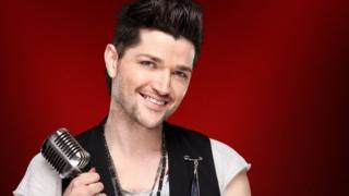 Danny O'Donoghue in his publicity photograph for BBC The Voice. He is wearing a white t-shirt and a smart black waistcoat. His hair is coiffed into an impressive quiff! He is holding a retro microphone and smiling.
