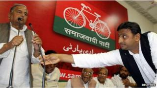 Akhilesh Yadav (R), the chief minister-designate of the northern Indian state of Uttar Pradesh and state party president adjusts microphone for his father, the Samajwadi Party President Mulayam Singh Yadav