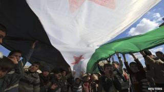 Children hold up a the green, white and black flag of the former Syrian Republic at an anti-government protest in Idlib province (2 March 2012)