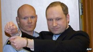 Anders Behring Breivik (right) with a police guard arrives in court in Oslo, 6 February