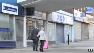 A couple walk past a row of closed shops