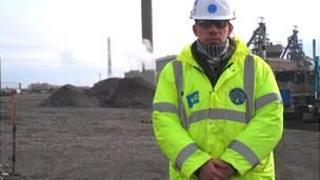 A picture of Kerry Jones in a high-vis jacket and hard hat standing in front of a work site.