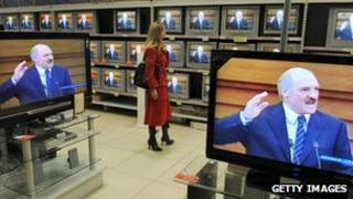 A Belarussian woman watches President Alexander Lukashenko giving his annual address on television at a Minsk electronics store