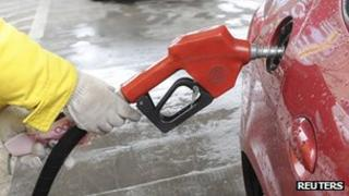 An employee holds 100 yuan banknotes as she fills its tank with petrol at a gas station in Hefei, Anhui, 20 March 2012