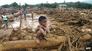 Child sits on tree in flood
