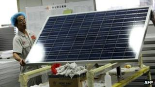 Workers lift a solar panel in a factory in Baoding, Hebei (file photo)