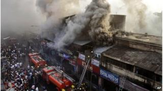 Indian firefighters work to extinguish a fire as smoke billows from a market building in Kolkata, India, Thursday, March 22, 2012.