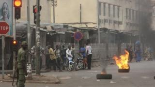 A soldier participating in a mutiny stands near civilians and burning tires lit in support of the mutiny, in Bamako, Mali Wednesday March 21 2012