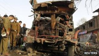Policemen stand near the wreckage of a truck after the car bomb explosion in Bijbehara, south of Srinagar March 22, 2012.