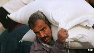 A Palestinian collects food aid. File photo