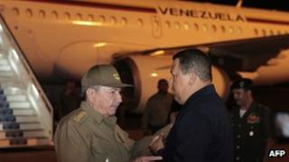 Hugo Chavez (r) is greeted by Cuban President Raul Castro on arrival in Havana