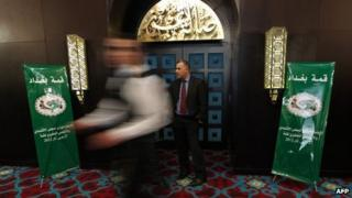 A man walks past a security guard at the venue of a meeting of Arab League finance ministers in Baghdad (27 March 2012)