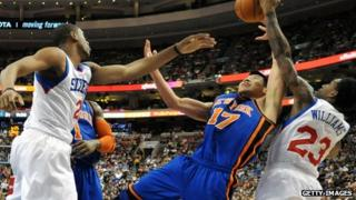 Jeremy Lin (centre) of the New York Knicks battles for a rebound with Thaddeus Young and Lou Williams of the Philadelphia 76ers