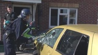 A police officer smashes a car window to gain entry to the vehicle