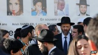 Jews gather beneath photos of the victims of the massacre at the Ozar Hatorah Jewish school in Toulouse, 25 March
