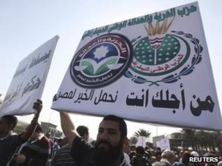 "A man holds up a poster showing the logos of the Muslim Brotherhood's Freedom and Justice Party and the former ruling National Democratic Party, which says: ""The Freedom and Justice party is now the NDP."""