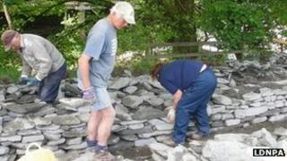 People building a dry stone wall. Photo: Lake District National Park