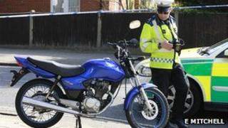 Policeman looking at motorbike