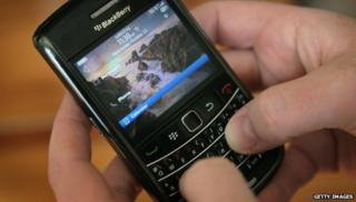 A person holds a Blackberry device
