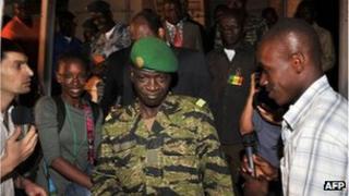 Malian junta leader captain Amadou Sanogo (C) leaves his office near Bamako on March 31
