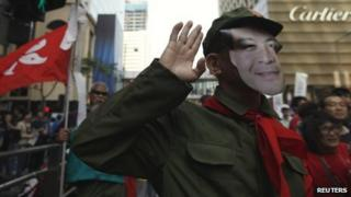 Protester wears a mask depicting CY Leung at a demonstration in Hong Kong on 1 April 2012