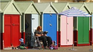 A woman outside beach huts