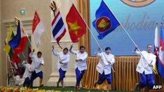 Performers carry flags of Asean member countries during a ceremony marking its 45th anniversary