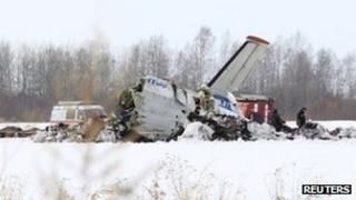 Emergency service workers investigate the wreckage of the UTair airlines ATR 72 passenger plane that crashed near the Siberian city of Tyumen, 2 April