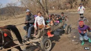 Roma children are taken home from school on a horse and cart north of Bucharest, 28 March 2012