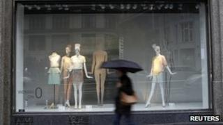Woman walking past a fashion store in Madrid