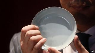 Sotheby's Asia Deputy Chairman Nicolas Chow holds the Ruyao washer