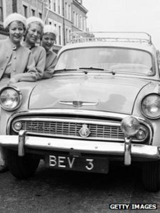 Women stand next to car with personalised number plates in June 1958