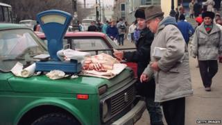 A street vendor sells meat displayed on the hood of a Lada car in Moscow on 30 March 1993