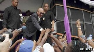 Suriname's President Desi Bouterse greets supporters that have gathered in front of Parliament in Paramaribo March, 23, 2012.
