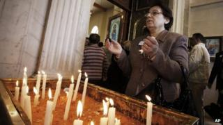 A woman prays on Palm Sunday in a church in Damascus, 1 April 2012