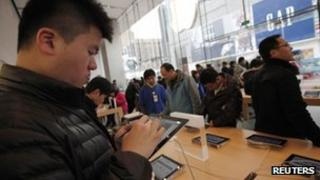 A man tests out an iPad at an Apple shop in Shanghai, 28 February 2012