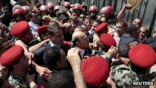Egypt's former vice president Omar Suleiman (C), is mobbed at the Elections Commission (HPEC) headquarters in Cairo, 8 April 2012