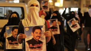 Bahraini anti-government protesters carry images of jailed hunger-striker Abdulhadi al-Khawaja during a demonstration outside the Interior Ministry in Manama (8 April 2012)