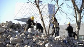 Workers demolish an old house at a construction site in Beijing, with the new China Central Television (CCTV) headquarters building in vision (file photo)